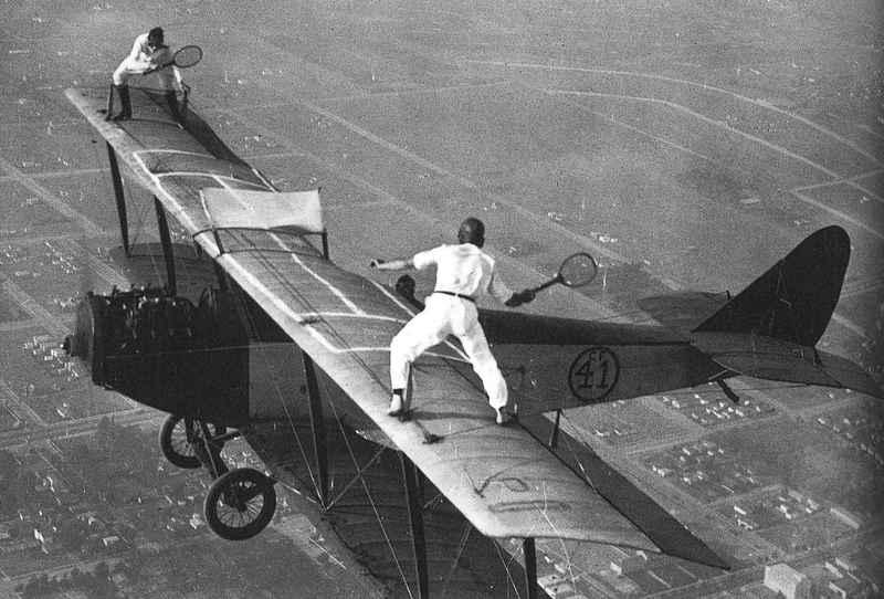 40 Amazing Historical Pictures - Two men play tennis on the wings of a bi-plane, c.1920
