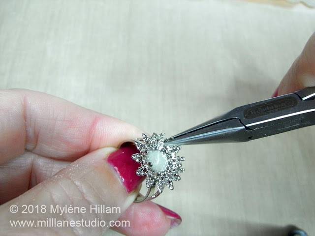 Use the chain nose pliers to open out the claws of the filigree ring base so the bead will fit.