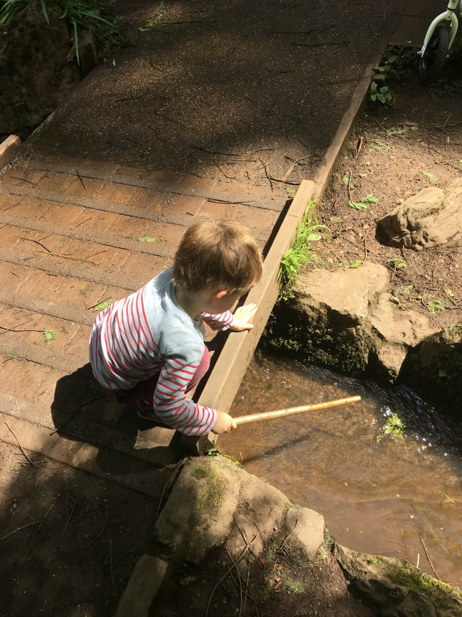toddler-playing-with-stick-in-water-at-cefn-onn-park