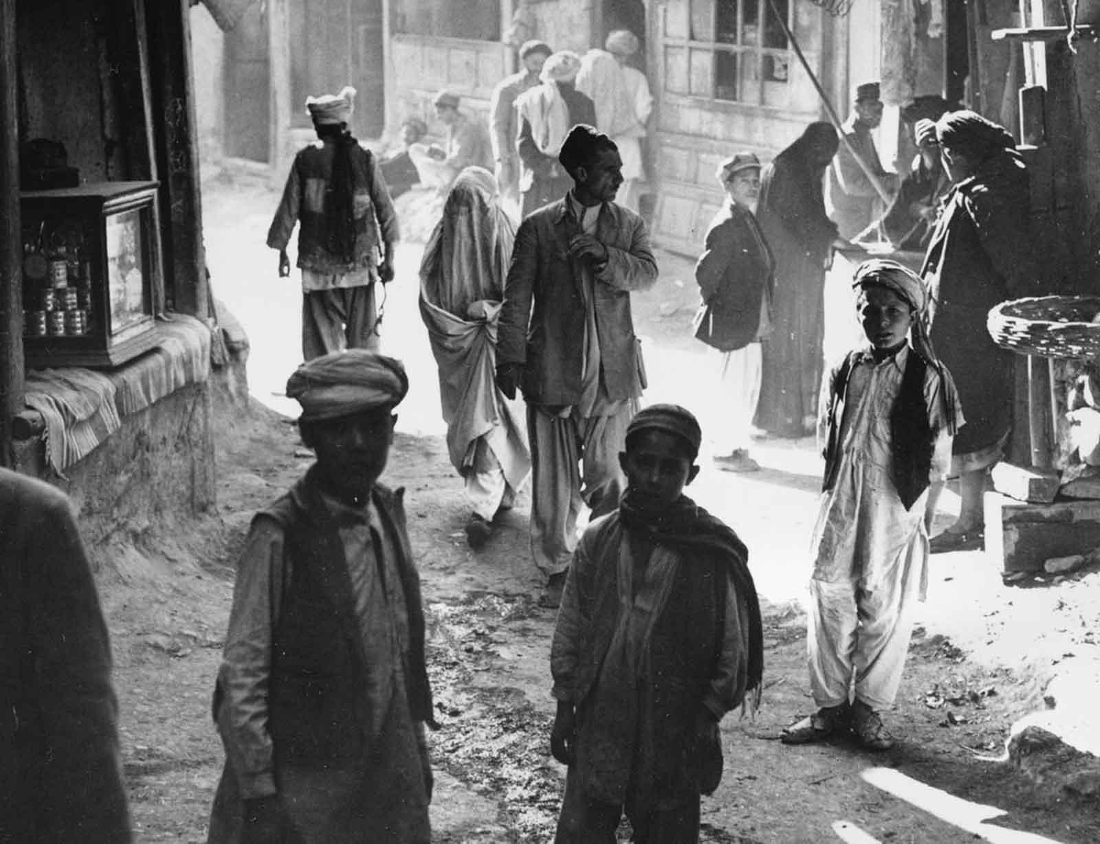 Muchachos, hombres y una mujer afganos caminan por una calle en Kabul, Afganistán, el 26 de marzo de 1954.