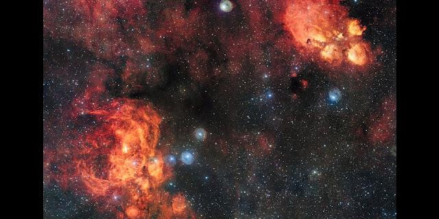 This spectacular image from the VLT Survey Telescope shows the Cat's Paw Nebula (NGC 6334, upper right) and the Lobster Nebula (NGC 6357, lower left). These dramatic objects are regions of active star formation where the hot young stars are causing the surrounding hydrogen gas to glow red. The very rich field of view also includes dark clouds of dust. With around two billion pixels this is one of the largest images ever released by ESO. Credit: ESO