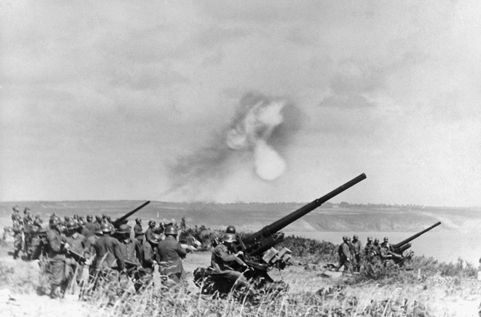 German Anti-Aircraft guns belch smoke somewhere along the Channel coast of France, on January 19, 1941.
