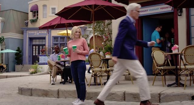 Eleanor lleva dos tazas de café frente a la yogurteria