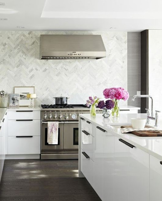stainless hood on marble white countertops over white cabinets