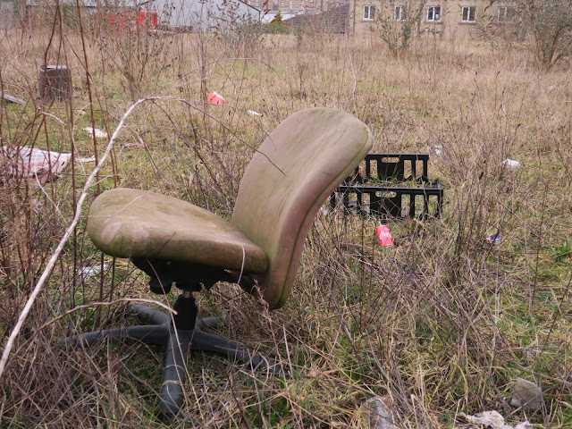 Padded office chair on waste ground in the evening.