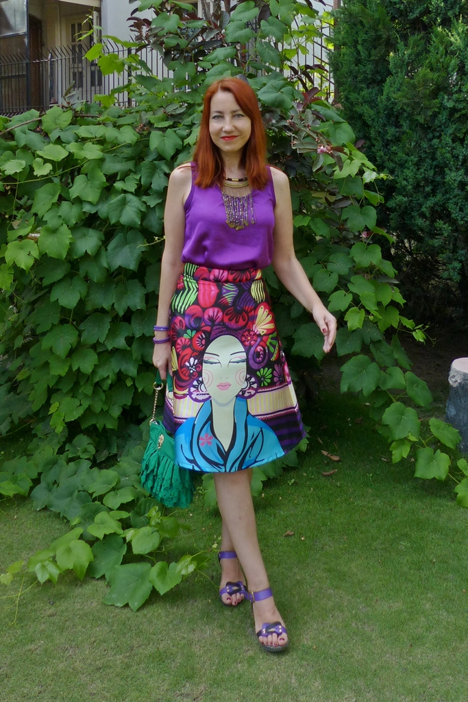 printed A-line skirt with purple top and beaded necklace
