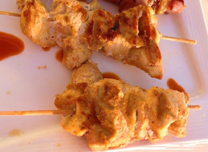 this is a grilled chicken boneless breast on a stick called souvlaki and it is served with cucumber sauce a greek dish
