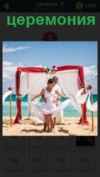 Женщина и мужчина в белых одеждах готовятся к церемонии своей свадьбы на берегу моря в небольшом шатре