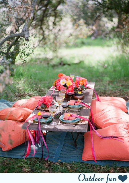This adorable outdoor picnic set up with flowers and colorful decor is adorable.
