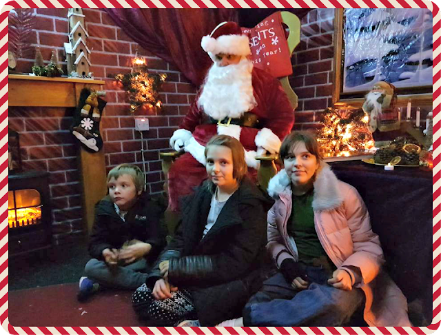 Three children sitting at the feet of Father Christmas in his grotto, with a festive fireplace to the left of the picture