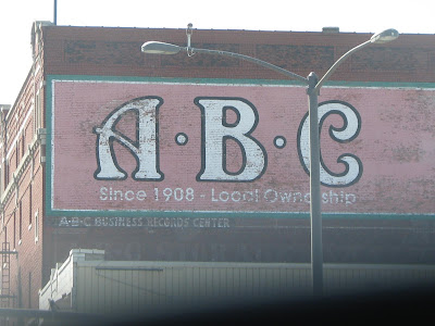 "A black and white photo of the side of a building with ""ABC"" on the billboard on its side."