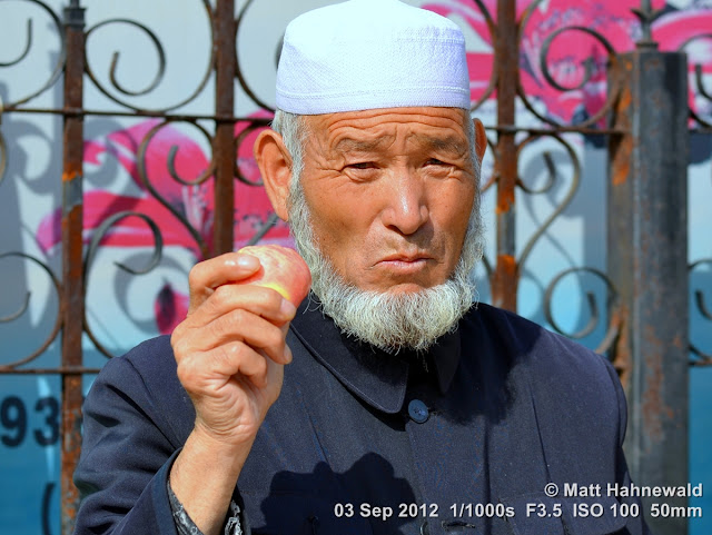 street portrait, headshot, China, Xi'an, Hui Muslims, Hui Muslim man, taqiyah, white skullcap, kufi, Muslim beard, rose apple, liánwù
