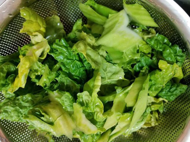 福岡で定番のカツオ菜をちぎって洗ってボールで水切りをしている写真