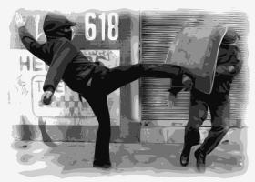 A protester kicking a riot policeman.