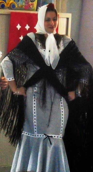Joven ataviada con vestido de chulapa hasta los pies, pañuelo blanco en la cabeza con clavel rojo, mantón negro y pose en jarras
