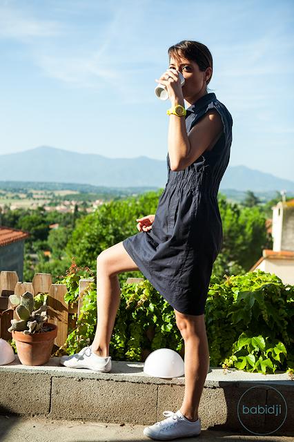 babidji debout sur sa terrasse face aux montagnes en train de boire son thé