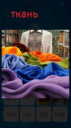 На столе лежит разнообразная ткань разных цветов