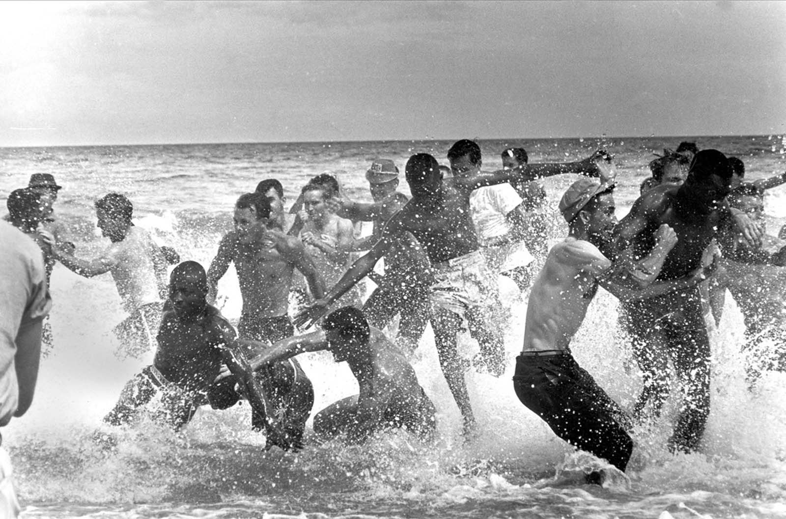 A group of white segregationists attack a group of blacks as they began to swim at the St. Augustine Beach, Florida, on June 25, 1964. Police moved in and broke up the fighting.