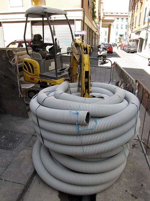 The fight of the little excavator against the huge corrugated pipe, via Oberdan, Livorno