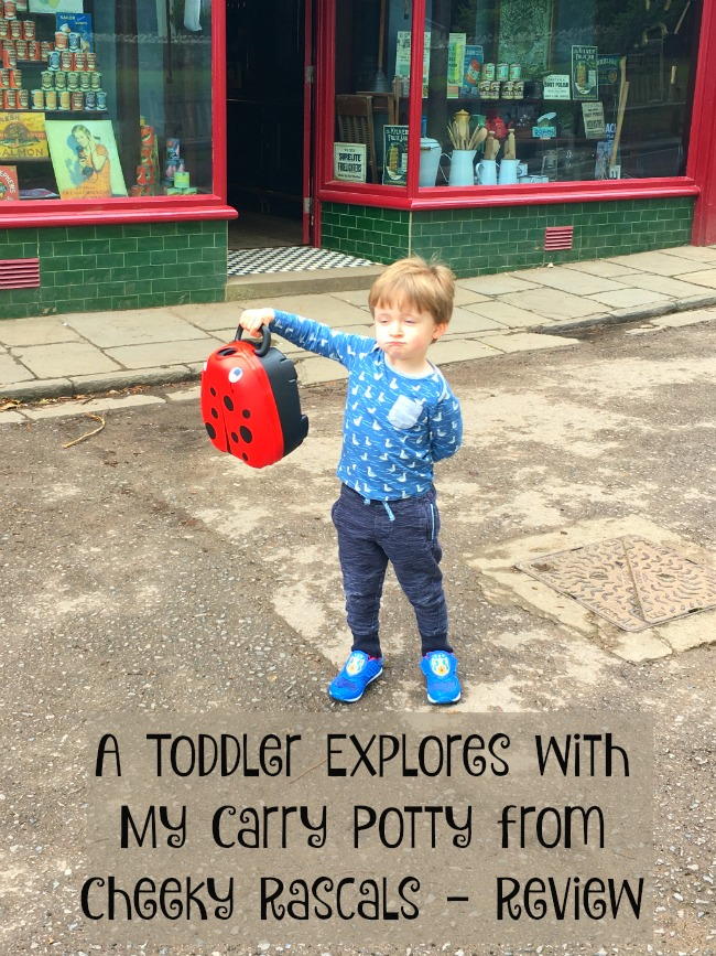 A-Toddler-Explores-with-My-Carry-Potty-from-Cheeky-Rascals-Review-text-over-image-of-toddler-holding-potty-at-st-Fagans-Museum-gwalia-stores
