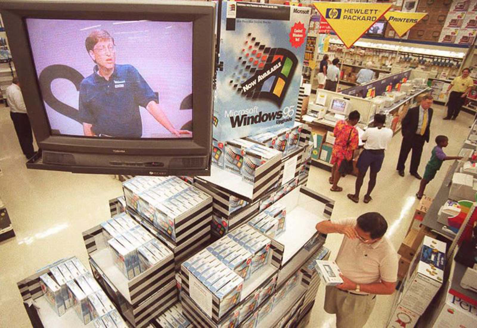 Microsoft CEO Bill Gates speaks on a television above a Windows 95 display at a store in Vienna, Virginia.