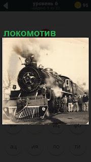 старый локомотив и люди рядом с ним