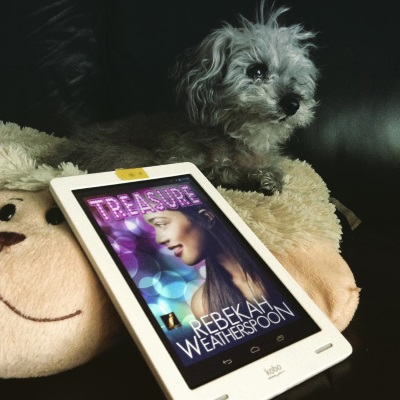 Murchie leans slightly off his sheep-shaped pillow. Below him, propped up against the sheep's head, is a white Kobo with Treasure's cover on its screen. The cover features a young, smiling black girl with long hair. She appears in profile against a constellation of purple, blue, and yellow light circles.