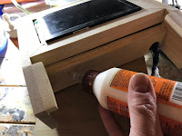 Applying glue to the bottom of the screen cabinet