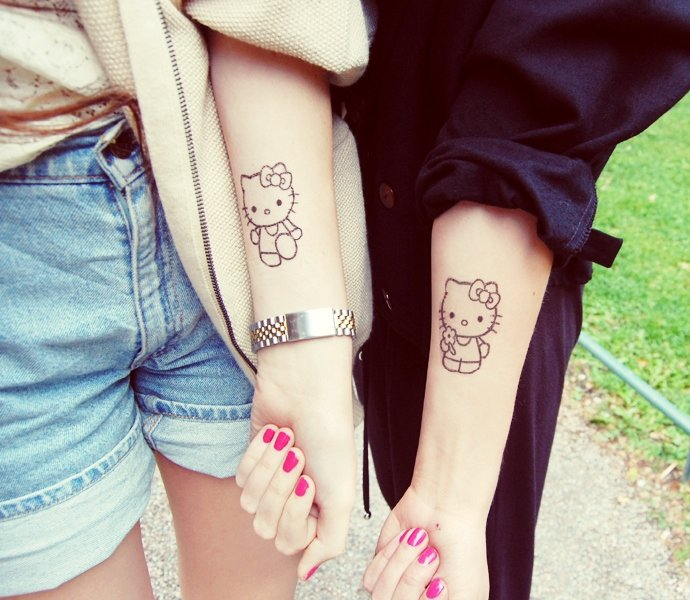 dos brazos de dos adolescentes, vemos en cada uno un tatuaje de hello kitty