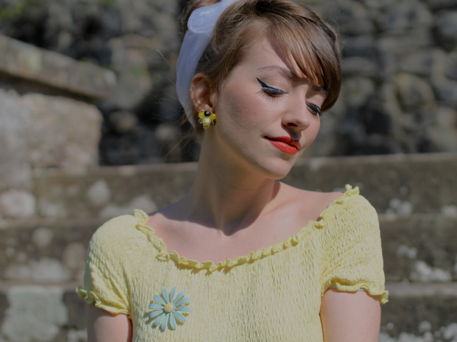 CiCi wearing a yellow top and cute brooch from Chronically Vintage