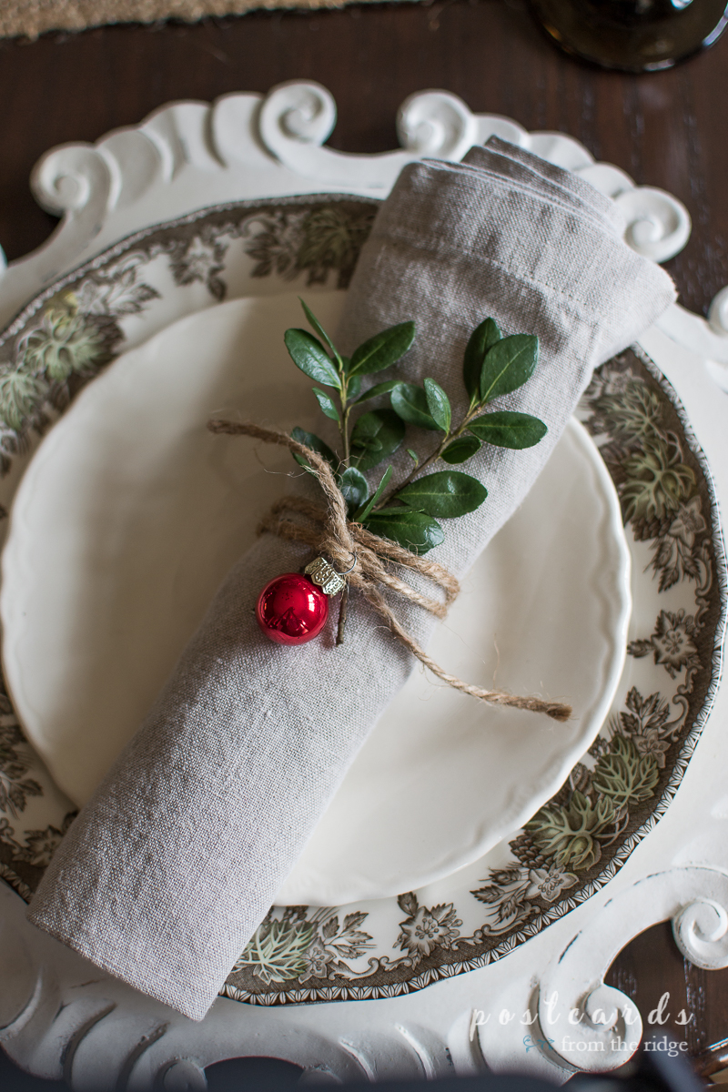 The little ornament and boxwood clippings are the perfect finish for this Christmas table setting.