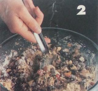 Mezclando todos los ingredientes para preparar el bizcocho de frutas con licor