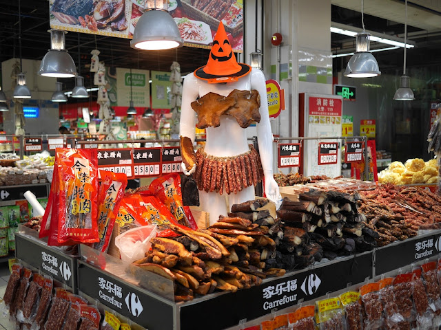 female mannequin dressed in dried meats and wearing a Halloween witch hat