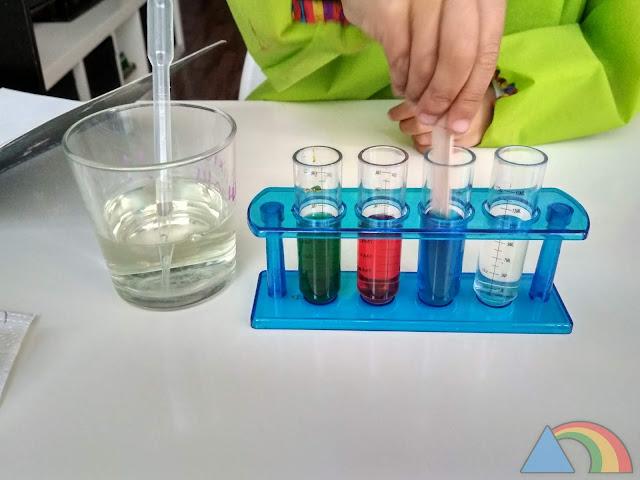 Removiendo el contenido del tubo de ensayo para disolver la lejía con el agua coloreada