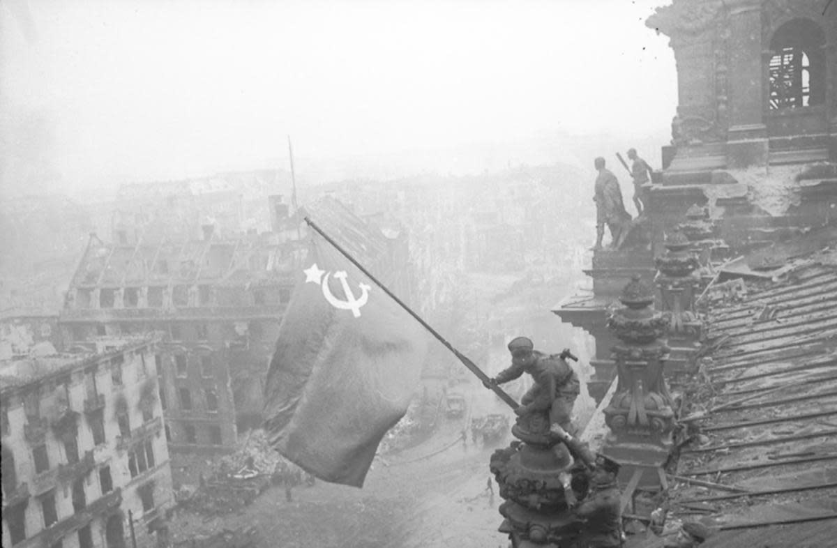The famous photo of Soviet soldiers over Reichstag during the Battle of Berlin, which was later revealed to be staged and altered.