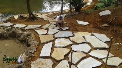 Bizzarri trabalhando, fazendo a execução de um lago de carpas com pedras ornamentais, tipo pedra moledo e em um dos lados do lago o piso com pedra e grama, tipo pedra cacão de São Tomé. Na foto, Bizzarri fazendo a execução do piso com pedra. 29 de março de 2017.