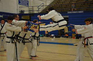A black belt breaking two boards with a twin front kick