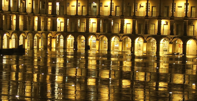 Lights of the Piece Hall balconies in Halifax reflected in the wet courtyard below.