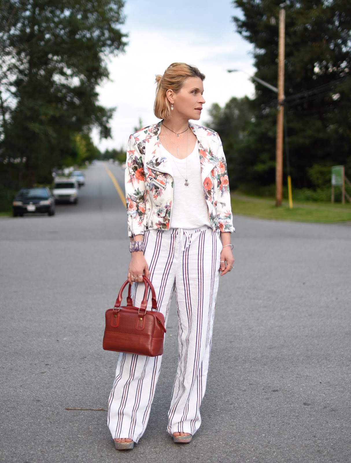 styling striped drawstring linen trousers with a slouchy tee, floral moto jacket, and Elvis & Kresse box bag