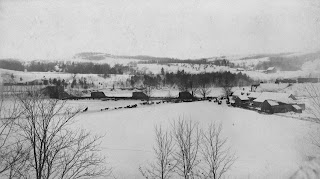 A photograph of a house amid a snowy field.