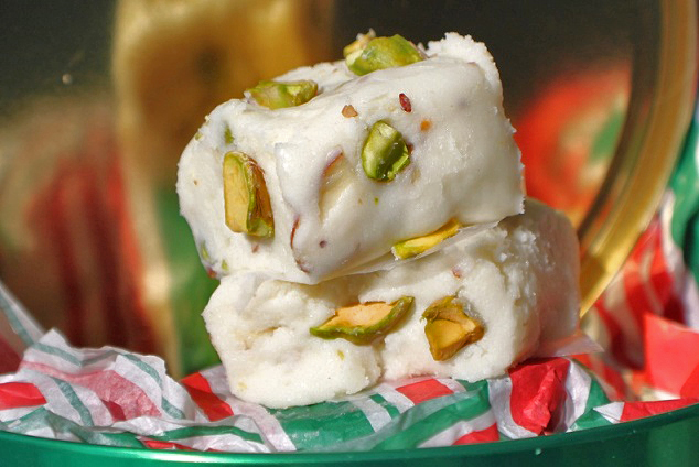 this is an easy how to make white chocolate amaretto fudge with pistachios in it in a green white and red paper Christmas tins for gift giving