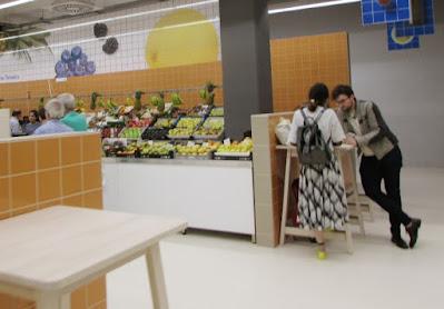 casal numa mesa junto à banca de frutas no Mercado Temporário do Bolhão