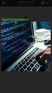 Программист за ноутбуком составляет программу нажимая на клавиатуре пальцами рук