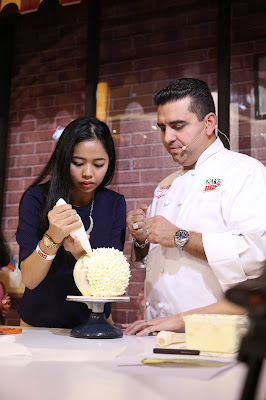 Buddy Valastro teaching a member of the audience how to decorate a durian cake. They are so lucky!