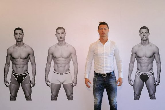 Cristiano Ronaldo poses in front of a poster promoting his new CR7 underwear range