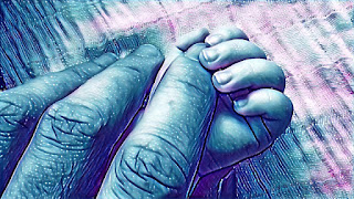 Una mano de bebé agarra una mano adulta