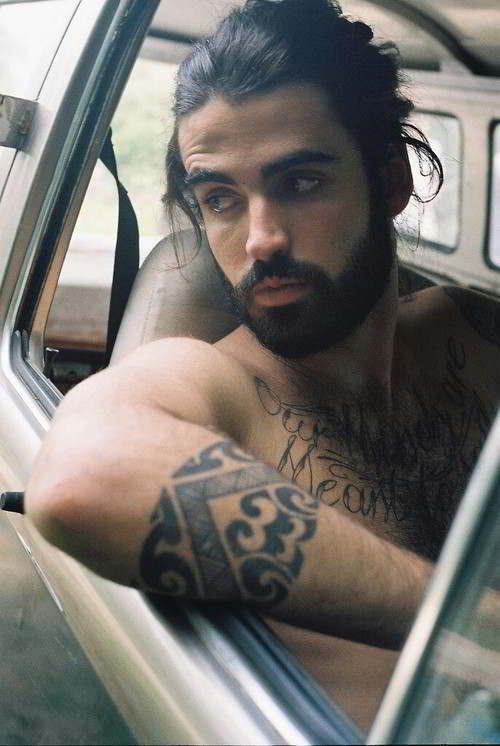 Foto de un joven modelo tatuado en su auto