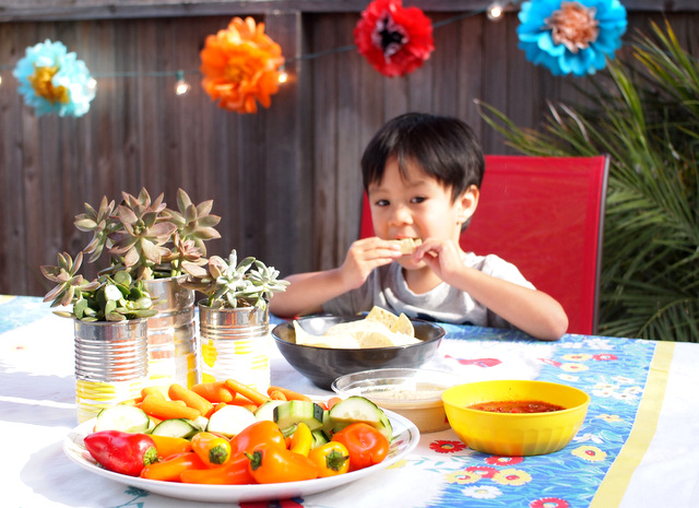 boy eating food at a tie-dye summer grill out party