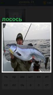 пойман лососьи и находится в руках у рыбака на судне