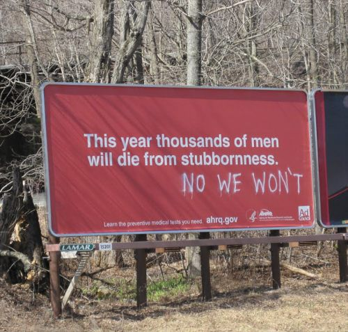 A billboard obviously vandalised by stubborn Men
